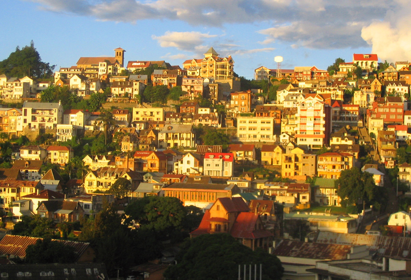 Town containing many buildings and trees on a hillside with a blue sky