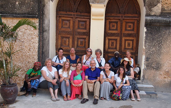 Group of Education Abroad students and faculty sitting with locals in Tanzania